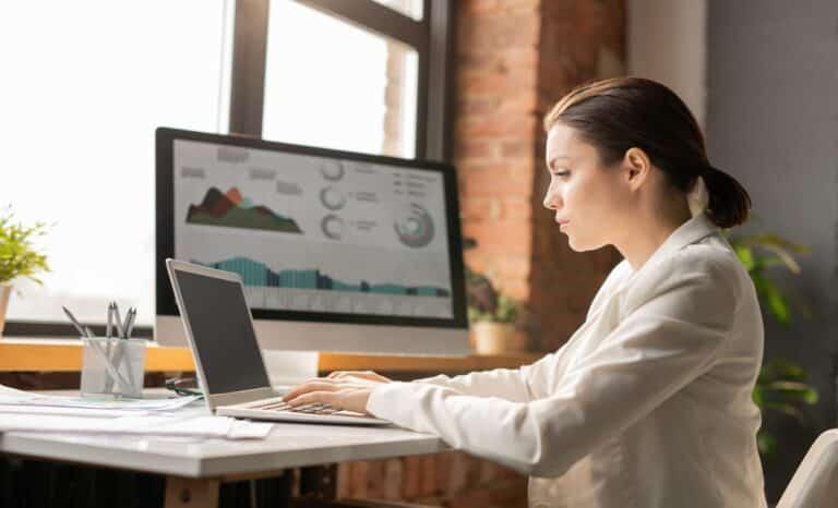 Mulher concentrada na análise de KPIs para a gestão de telecom enquanto está sentada na frente do laptop no escritório