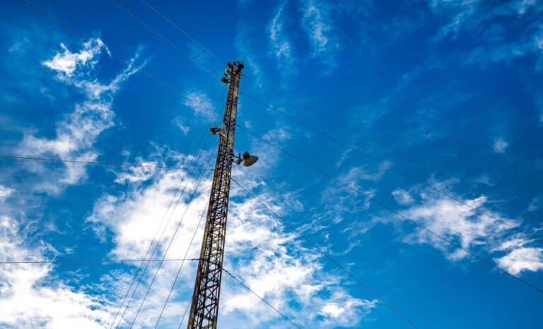 Torre de telecomunicações com céu azul e algumas nuvens brancas ao fundo