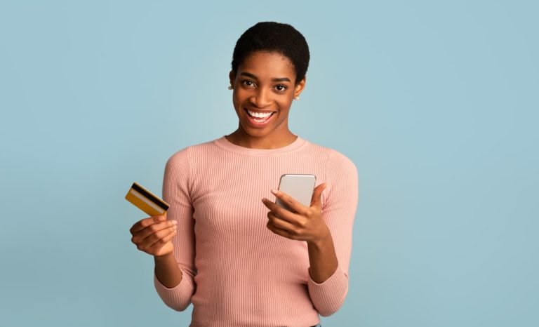 Mulher segurando um celular em uma das mãos e um cartão de crédito na outra mão