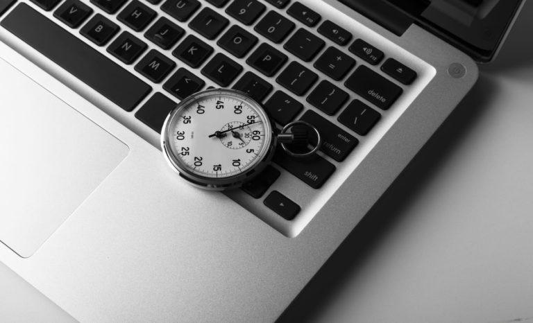 Laptop prata com cronômetro sobre o teclado, marcando o tempo de resposta acordado no SLA