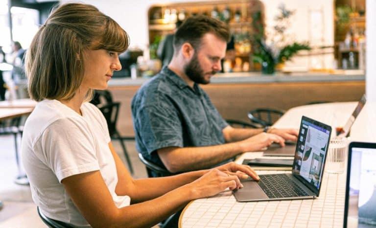 Homem e mulher trabalhando em seus notebooks