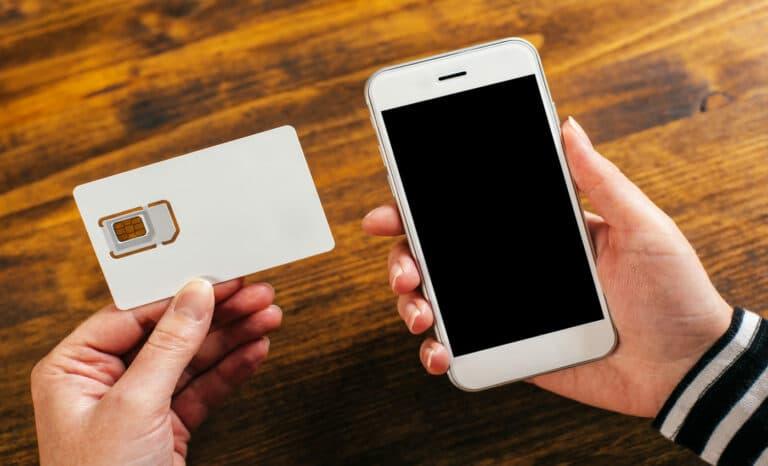 Mulher segurando smartphone e novo cartão SIM, após a portabilidade
