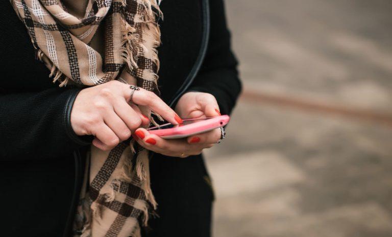 Close-up da mão de uma mulher usando telefone celular para realizar cadastro no Não Me Perturbe